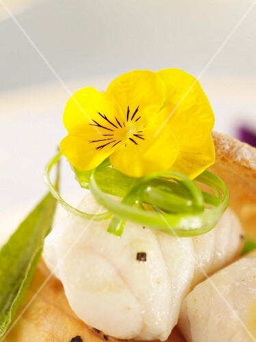 Steamed fish fillet with an edible flower