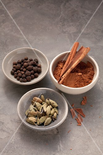 Three dishes of spices: allspice, cardamom and cinnamon