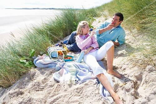 Young couple having picnic at beach