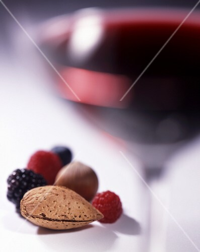 A glass of red wine with berries and nuts
