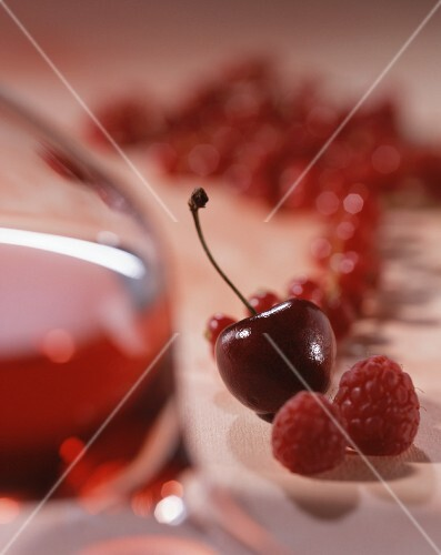 A glass of red wine with raspberries, cherries and redcurrants