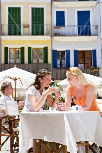 Women drinking coffee and water at sunny, outdoor cafe