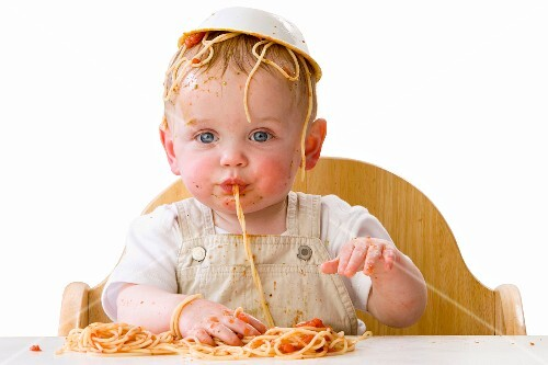 Messy baby playing with spaghetti