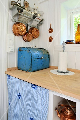 A vintage bread bin and copper cooking and baking utensils, in a renovated kitchen with a pale wood worktop and white wood-panelled walls