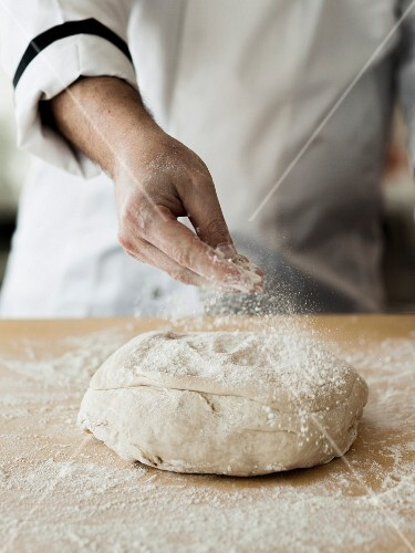 Fresh pizza dough being dusted with flour