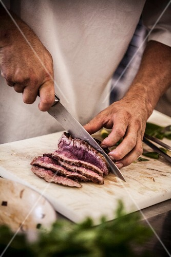 A chef cutting roast beef into thin slices