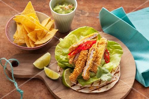 Strips of schnitzel in a nacho crumb coating, guacamole and tortillas