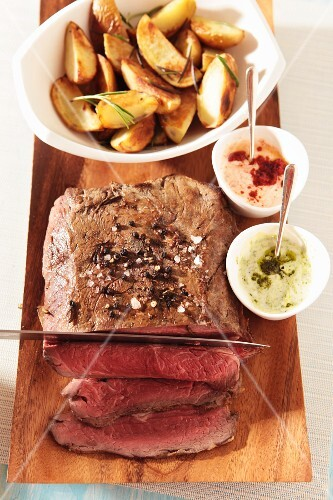 Roast beef with roast potatoes and two sauces