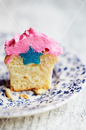 A cupcake with a blue star inside it and pink icing