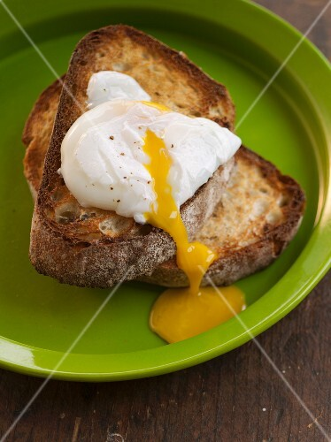 Poached Egg Over Toast with Runny Yolk; On a Green Plate