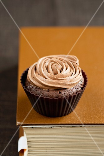 A chocolate cupcake with a rose made of icing