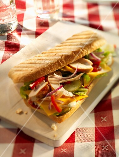 Chicken, onion, pepper, gherkins, cheese slices, lettuce and ketchup in a baguette on a wooden board
