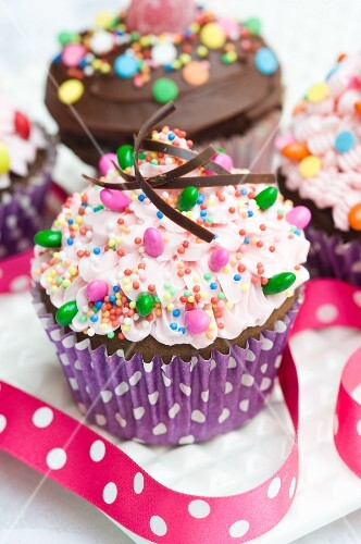 Two cupcakes topped with pink buttercream icing, chocolate icing and sweets