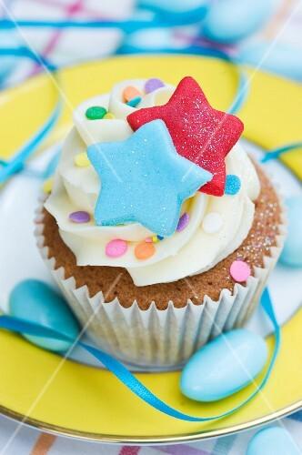 A vanilla cupcake with colourful stars, sugar confetti and blue sugared almonds