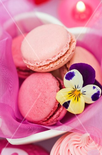 Strawberry and raspberry macaroons in a heart-shaped dish with a pansy