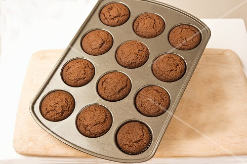 Chocolate muffins in a muffin tray on a chopping board