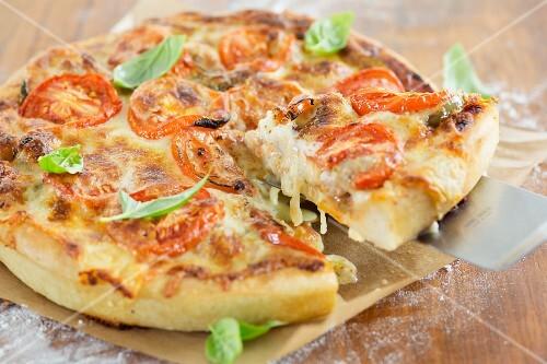 Deep Dish Pizza mit Basilikumblättern (Pizza mit hohem Rand, Chicago, USA), ein Stück auf Pizzaheber