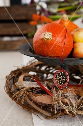An autumnal table decoration with pumpkins and a dream-catcher