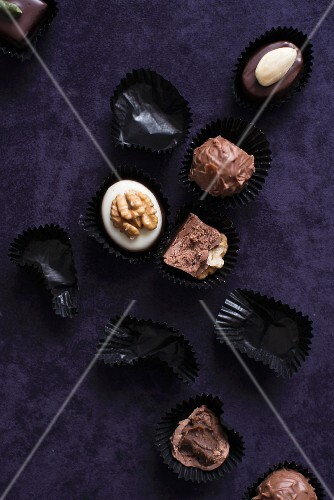 An assortment of filled chocolates and empty chocolate cases