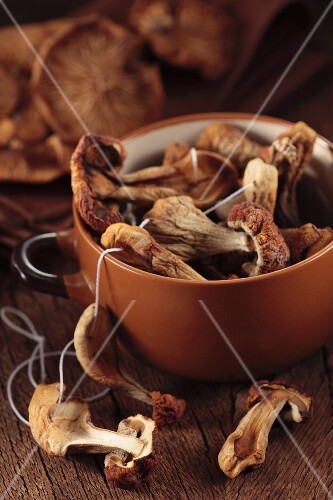 Dried porcini mushrooms in a bowl on a wooden surface