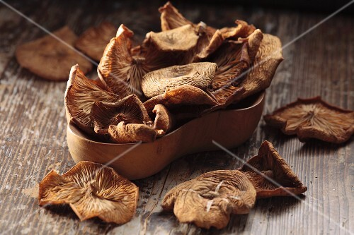 Dried honey fungus in a wooden bowl on a wooden surface