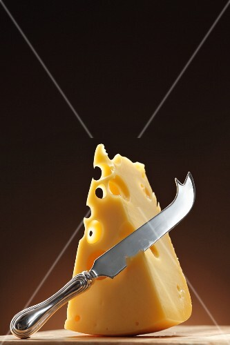 A wedge of Emmental cheese and a cheese knife