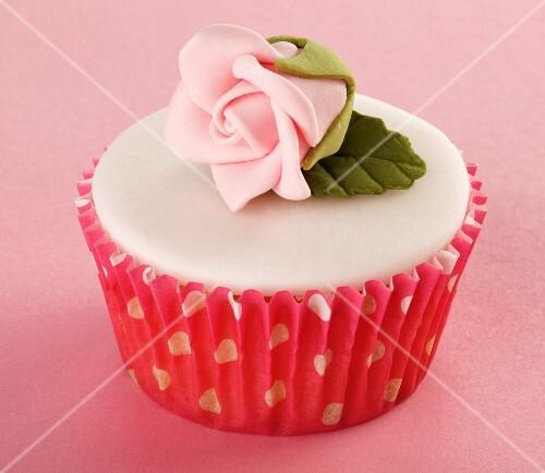 A cupcake with white glaze and a sugar rose