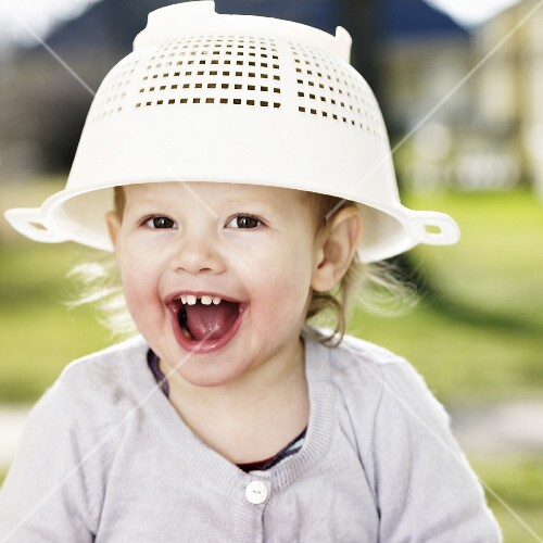 A little girl with a plastic colander on her head