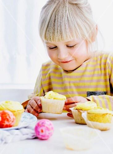 A smiling girl admiring cupcakes