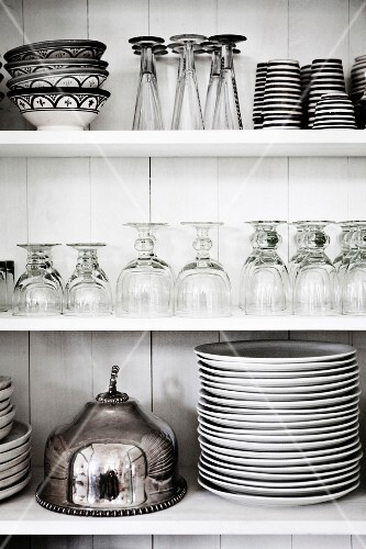 Kitchen shelves with glasses, crockery and a serving cloche