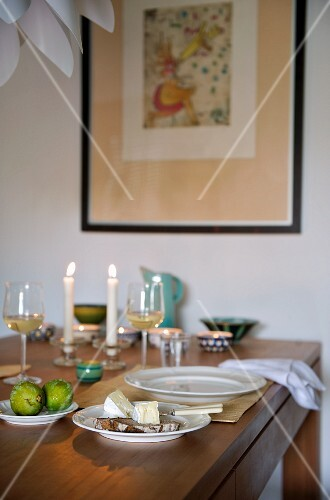 Table set for two with candlelight, glasses of wine and bread and cheese
