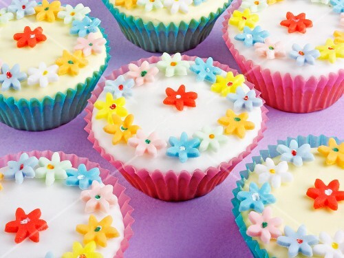 Cupcakes decorated with colourful sugar flowers