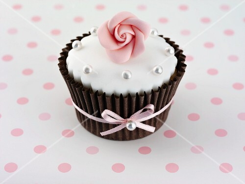 A cupcake decorated with a sugar rose and silver balls