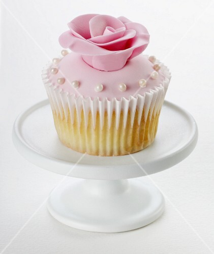 A cupcake with pink glaze, a sugar rose and small sugar pearls