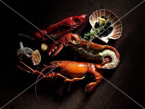 A still life including lobster, olives and thyme