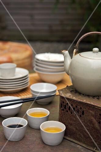 Tea bowls next to a teapot on a vintage tea warmer