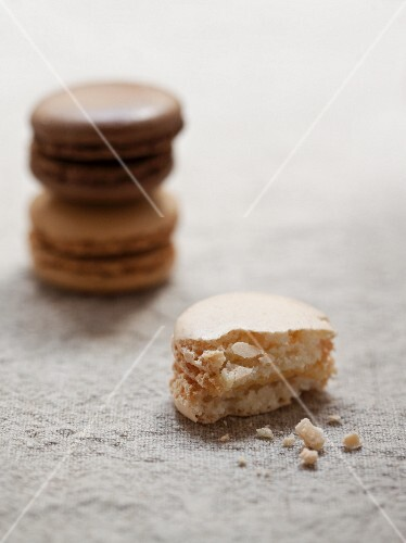 Three macaroons, one of which has a bite missing