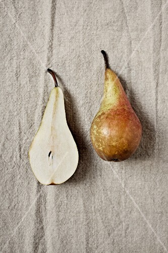 A whole pear and a pear half on a linen cloth