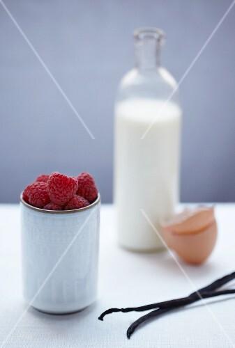 Raspberries, vanilla pods, an eggshell and a bottle of milk