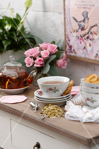 Tea, dried chamomile and pastries on cabinet