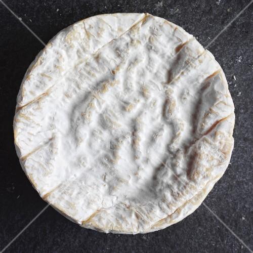 A whole Camembert on a slate slab