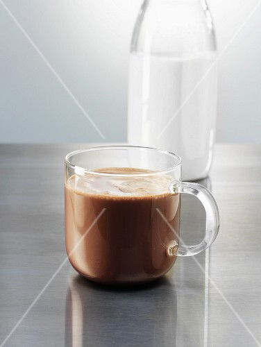 A glass cup of hot cocoa next to a bottle of milk