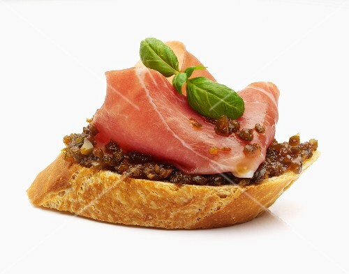 A slice of baguette topped with olive purée, Parma ham and basil leaves