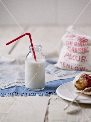 A bottle of milk with a drinking straw, a bag of flour and a sweet pastry