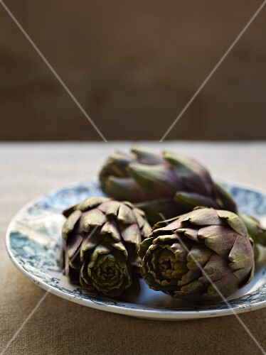 Three artichokes on a plate