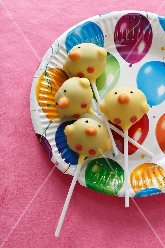 Cake pops (chicks) on a colourful paper plate