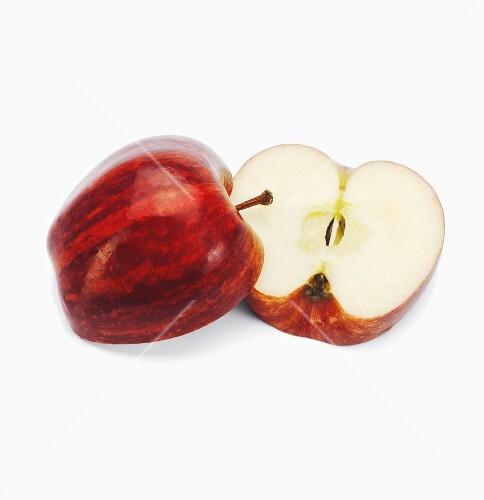 A Braeburn apple, halved, against a white background