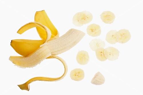 A half-peeled banana and slices of banana