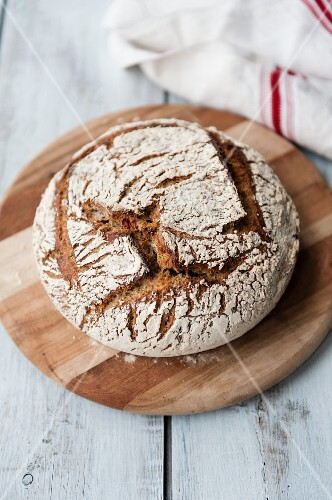 Home-made sourdough bread on a round chopping board