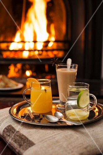 Three different hot drinks on a tray in front of the fire